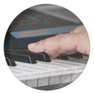 mano izquierda eléctrica del piano que juega diseñ platos