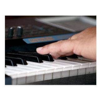 mano izquierda eléctrica del piano que juega diseñ postales