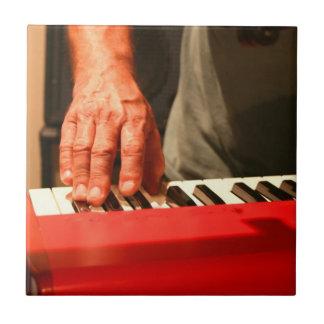 mano que juega al músico rojo del varón del teclad tejas
