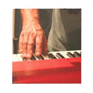 mano que juega al músico rojo del varón del teclad blocs de notas