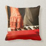 mano que juega al músico rojo del varón del teclad cojin