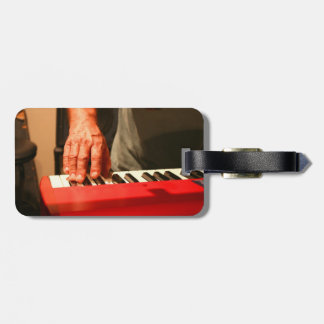mano que juega al músico rojo del varón del teclad etiquetas de maletas