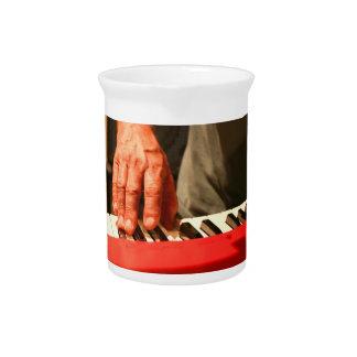 mano que juega al músico rojo del varón del teclad jarrones