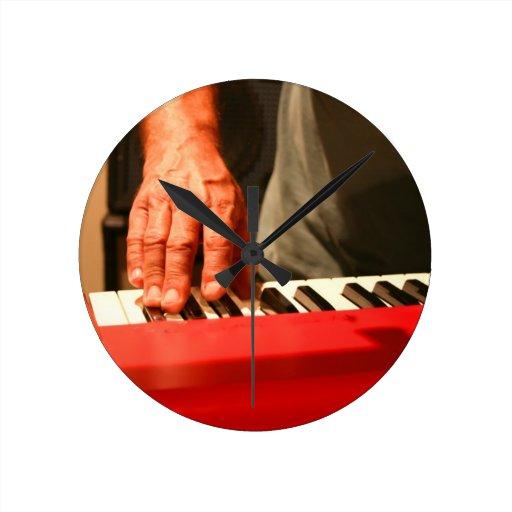 mano que juega al músico rojo del varón del teclad relojes