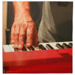 mano que juega al músico rojo del varón del teclad servilleta de papel