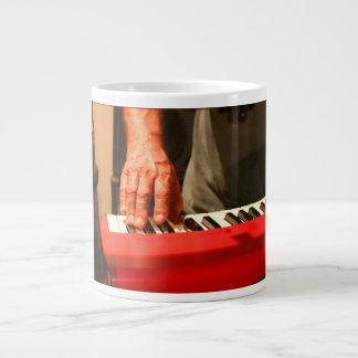 mano que juega al músico rojo del varón del teclad taza grande