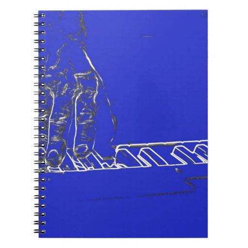 mano que juega el esquema blanco azul de la tinta  spiral notebook