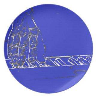 mano que juega el esquema blanco azul de la tinta  platos para fiestas