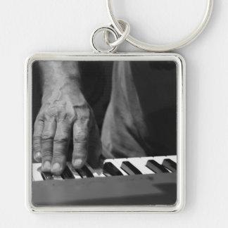 mano que juega música del varón del bw del teclado llavero