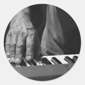 mano que juega música del varón del bw del teclado etiqueta redonda