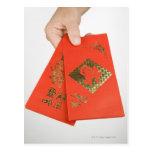 Mano que sostiene el sobre chino del dinero postales