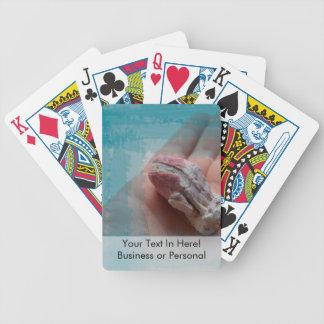 mano que sostiene el trullo del seashell de la baraja de cartas
