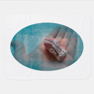 mano que sostiene el trullo del seashell de la mantas de bebé