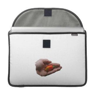 Mano que sostiene un pimiento picante del habanero fundas para macbook pro