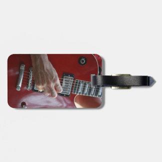 Mano que toca la guitarra eléctrica roja cerca de etiquetas de equipaje