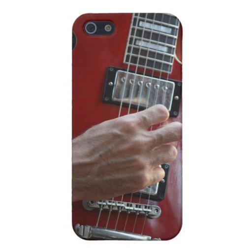 Mano que toca la guitarra eléctrica roja cerca de  iPhone 5 fundas