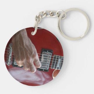 Mano que toca la guitarra eléctrica roja cerca de llavero redondo acrílico a doble cara