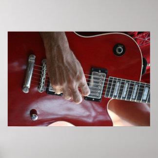 Mano que toca la guitarra eléctrica roja cerca de  poster