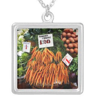 Manojos de zanahorias y de verduras en mercado colgante