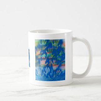 Manos anaranjadas en un fondo azul taza básica blanca