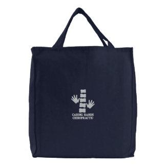 Manos de la quiropráctica y bolso bordado espina bolsa bordada