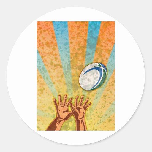 manos del jugador del rugbi que cogen la bola pegatina redonda