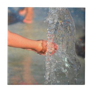 manos del niño en fuente de agua azulejos cerámicos