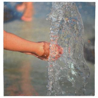 manos del niño en fuente de agua servilletas