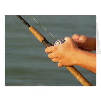 Manos del pescador con Rod y el carrete Tarjeta