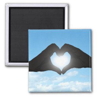 Manos en silueta de la forma del corazón en el iman para frigorífico