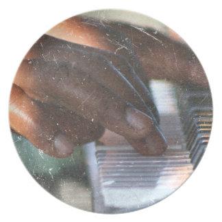manos oscuras de la piel que juegan grunge del tec plato para fiesta