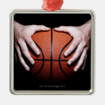 Manos que llevan a cabo un baloncesto adornos