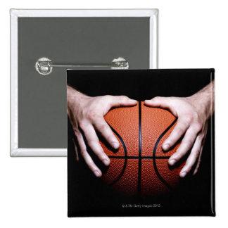 Manos que llevan a cabo un baloncesto pin cuadrado
