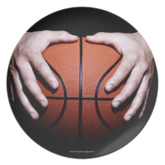 Manos que llevan a cabo un baloncesto platos para fiestas