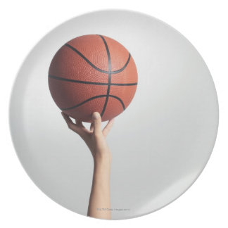 Manos que llevan a cabo un baloncesto, primer de platos para fiestas
