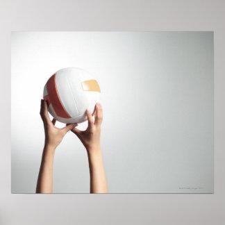 Manos que llevan a cabo un voleibol, primer de las posters