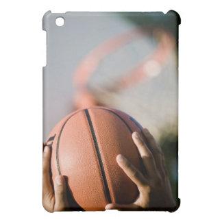 Manos que tiran baloncesto al aire libre