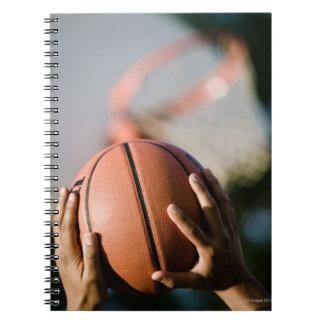 Manos que tiran baloncesto al aire libre cuadernos