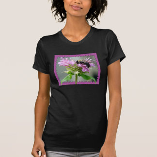 Manosee la abeja en la camisa de la flor del bálsa