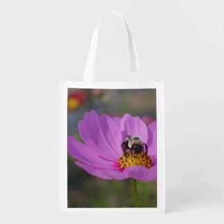 Manosee la abeja en la flor rosada del cosmos bolsas de la compra