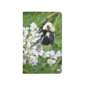 Manosee la abeja en las flores blancas cuadernos