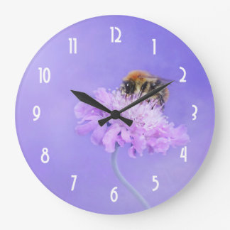 Manosee la abeja encaramada en una flor rosada reloj redondo grande
