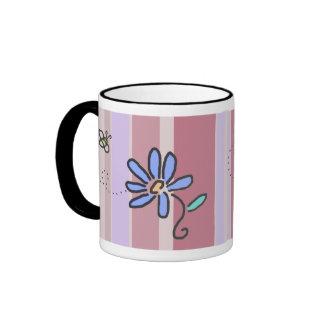 Manosee la abeja y la flor azul con las rayas de c taza
