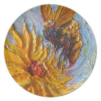 Manosee la abeja y la placa amarilla de la flor platos