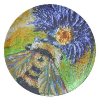 Manosee la abeja y la placa azul de la flor del as plato de comida