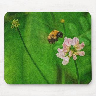 Manosee la flor del trébol del vuelo de la abeja tapete de raton