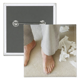 Man's feet surrounded by crumpled tissues button