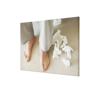 Man's feet surrounded by crumpled tissues canvas print