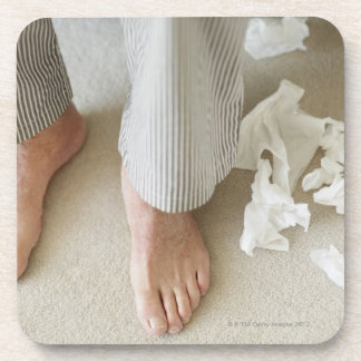 Man's feet surrounded by crumpled tissues drink coaster