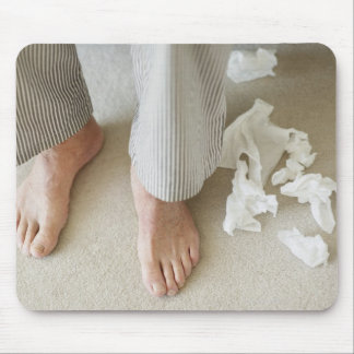 Man's feet surrounded by crumpled tissues mouse pad